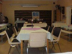 Isompi luokkahuone, tarjoilupöytä ja vieraat samassa tilassa
